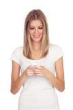 Muchacha rubia que mira su móvil Fotos de archivo