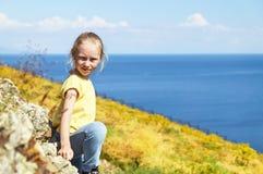 Muchacha rubia que presenta en la orilla de un lago Imagenes de archivo