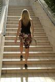 Muchacha rubia que recorre en las escaleras Fotos de archivo libres de regalías
