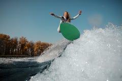Muchacha rubia que salta en el wakeboard verde en las rodillas de doblez imagenes de archivo