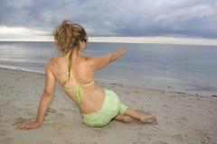 Muchacha rubia que señala al mar en puesta del sol Imagenes de archivo