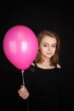 Muchacha rubia que señala con el globo rosado sobre negro Imagen de archivo libre de regalías