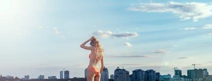 Muchacha rubia que se coloca en el traje de baño coralino, en el fondo de la ciudad imagenes de archivo
