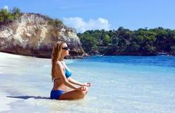 Muchacha rubia que se relaja en agua en la playa imagen de archivo