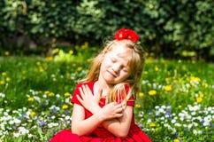 Muchacha rubia que se sienta en banco al lado del lago Imágenes de archivo libres de regalías