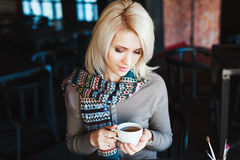 Muchacha rubia que se sienta en café con la taza de té Imágenes de archivo libres de regalías