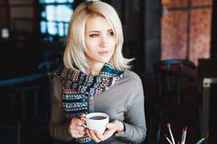 Muchacha rubia que se sienta en café con la taza de té Foto de archivo