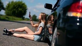 Muchacha rubia que se sienta en el camino cerca de su coche quebrado metrajes