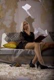 Muchacha rubia que se sienta en el sofá Imagen de archivo libre de regalías