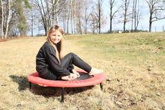 Muchacha rubia que se sienta en el trampolín Fotografía de archivo