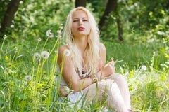 Muchacha rubia que se sienta en hierba Imágenes de archivo libres de regalías