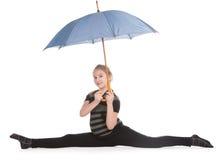 Muchacha rubia que se sienta en la guita y que sostiene el paraguas Foto de archivo libre de regalías