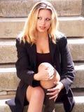 Muchacha rubia que se sienta en las escaleras Foto de archivo