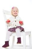 Muchacha rubia que se sienta en una silla con las manzanas rojas Fotografía de archivo
