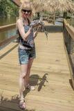 Muchacha rubia que sostiene en sus brazos un cocodrilo del bebé Foto de archivo libre de regalías