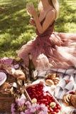 Muchacha rubia que tiene una comida campestre fotografía de archivo libre de regalías