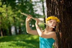 Muchacha rubia que toca la flauta en el parque Fotos de archivo