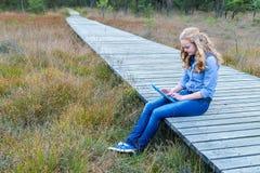 Muchacha rubia que trabaja en la tableta en la trayectoria de madera en naturaleza Fotografía de archivo libre de regalías