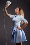 Muchacha rubia que usa el secador de pelo fotografía de archivo