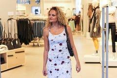 Muchacha rubia rizada atractiva que sale la moda y la tienda de ropa Fotografía de archivo libre de regalías