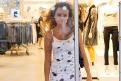 Muchacha rubia rizada atractiva que sale la moda y la tienda de ropa Foto de archivo libre de regalías