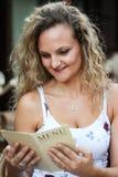 Muchacha rubia rizada atractiva que se sienta en un café y una lectura hombres Imagen de archivo