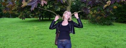 Muchacha rubia rusa que presenta cerca del árbol imagenes de archivo