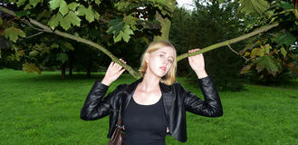 Muchacha rubia rusa que presenta cerca del árbol en chaqueta imágenes de archivo libres de regalías