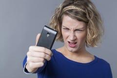 muchacha rubia 20s decepcionada sobre su imagen en smartphone Fotografía de archivo