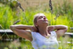 muchacha rubia 20s que disfruta del sol y del tiempo libre cerca del agua Imagen de archivo