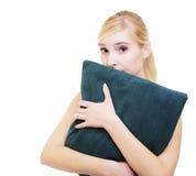 Muchacha rubia soñolienta con la almohada verde aislada sobre blanco Fotografía de archivo
