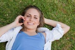 Muchacha rubia sonriente de los jóvenes que miente en ella detrás mientras que mira para arriba Fotos de archivo