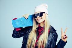 Muchacha rubia sonriente del adolescente en lentes de sol negros y sombrero rosado con el monopatín azul En el fondo blanco Foto de archivo