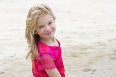 Muchacha rubia sonriente en la playa en día asoleado Imagenes de archivo