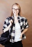 Muchacha rubia sonriente feliz joven del inconformista con la mochila lista a la escuela, concepto adolescente de la gente de la  Imagenes de archivo