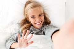 Muchacha rubia sonriente feliz que toma el selfie mientras que miente en cama Fotos de archivo