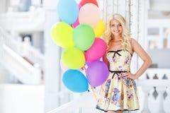 Muchacha rubia sonriente hermosa con los globos coloridos Imagen de archivo libre de regalías