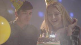 Muchacha rubia sonriente linda en el sombrero del cumpleaños que sopla hacia fuera velas en la torta, el hombre joven que se sien almacen de video