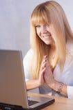 Muchacha rubia sonriente que charla en línea con el ordenador Foto de archivo