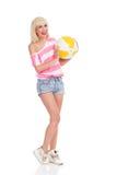 Muchacha rubia sonriente que sostiene una pelota de playa Imagenes de archivo
