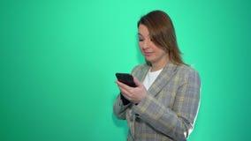 Muchacha rubia sorprendida que manda un SMS en el teléfono móvil mientras que se coloca aislado sobre fondo verde almacen de metraje de vídeo