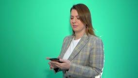 Muchacha rubia sorprendida que manda un SMS en el teléfono móvil mientras que se coloca aislado sobre fondo verde almacen de video