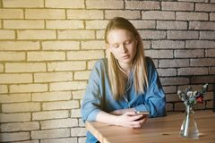 Muchacha rubia triste en la blusa azul que se sienta en la tabla en un café, l Imagen de archivo