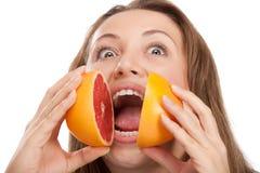 Muchacha rubia y linda con la naranja Imagen de archivo libre de regalías