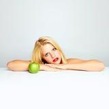 Muchacha rubia y manzana verde Imagen de archivo libre de regalías