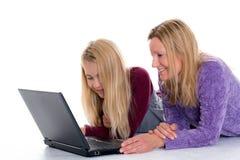 Muchacha rubia y su madre que usa el ordenador portátil Fotos de archivo