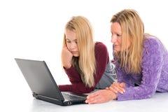 Muchacha rubia y su madre que usa el ordenador portátil Fotografía de archivo libre de regalías