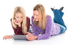 Muchacha rubia y su madre que usa la tableta foto de archivo