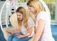 Muchacha rubia y su madre que usa la tableta junto Imagen de archivo libre de regalías