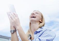 muchacha Rubio-cabelluda, tomando imágenes en el smartphone, sosteniéndolo con ambas manos, fondo del cielo Día, al aire libre Imagen de archivo libre de regalías